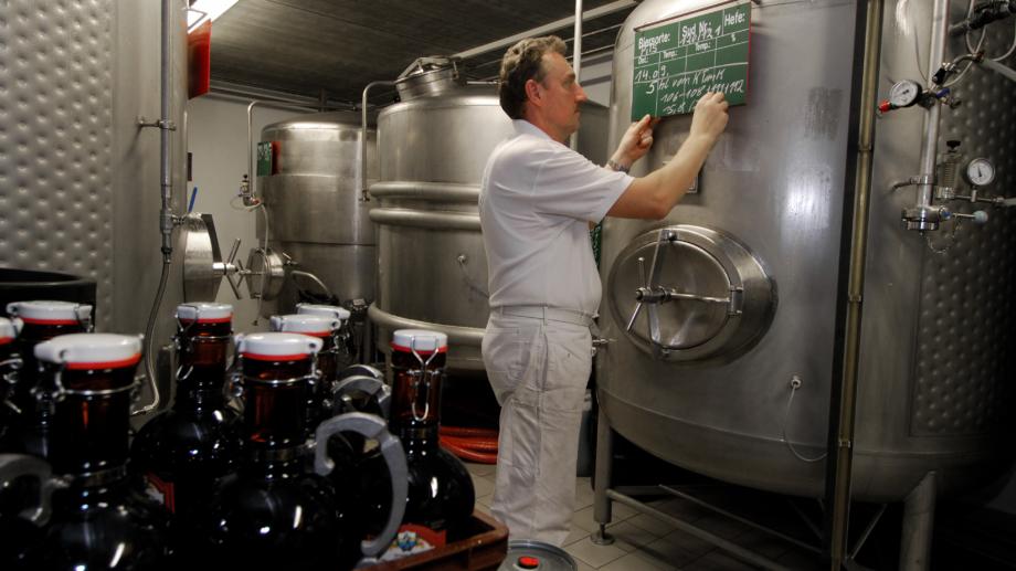 Brauer steht vor Brauereikesseln mit Bierflaschen im Vordergrund