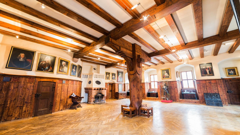 leerer Rittersaal mit Fachwerkdecke und mittelalterlichen Ausstellungstücken neben einem alten Kamin