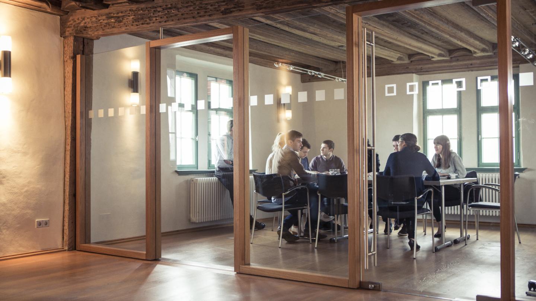 Tagende Menschen hinter einer Glaswand in einem kleinem Konferenzraum © Altes Schloss Dornburg, Foto: Guido Werner