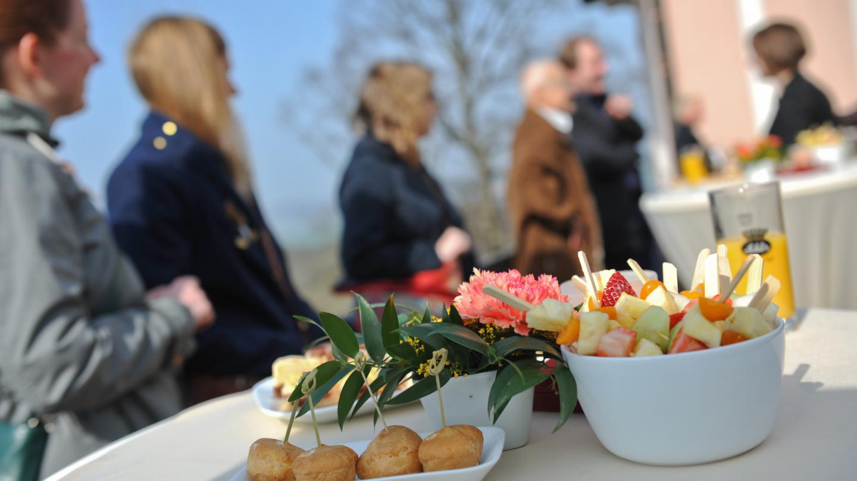 Tagungsgäste an Stehtischen mit verschiedem Fingerfood