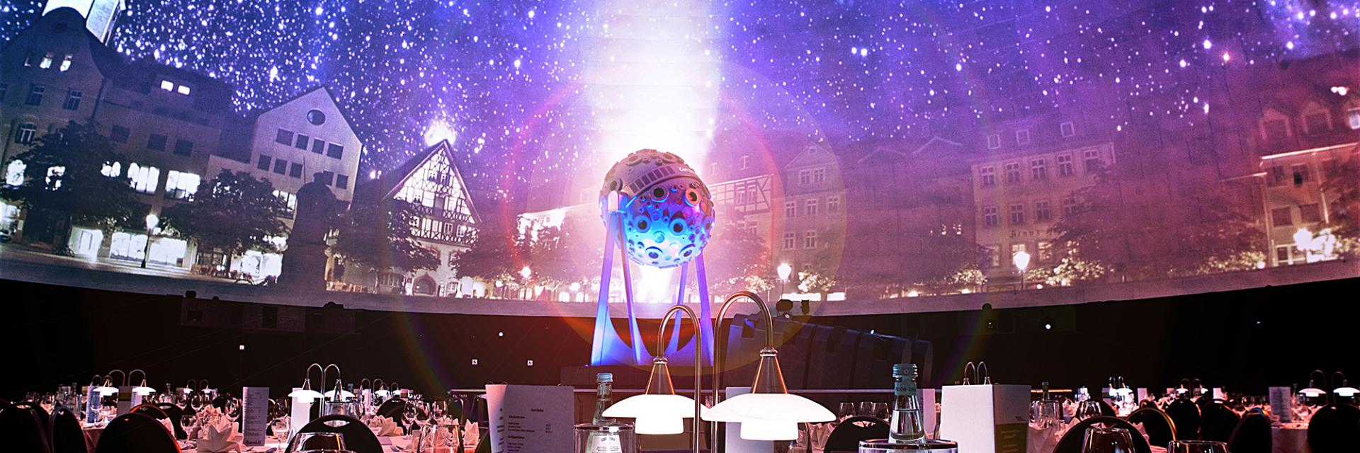 Tischgedeck mit Carl Zeiss Projektor im Hintergrund unter der sternenerleuchteten Kuppel