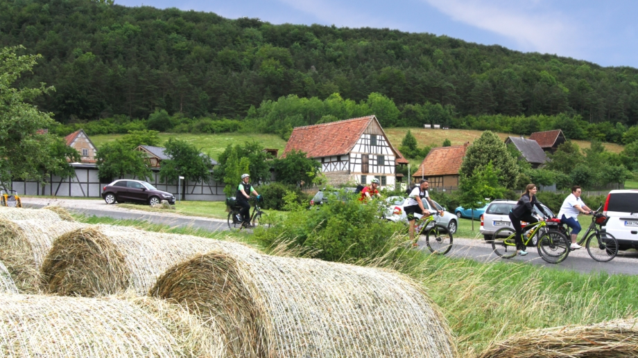 Radfahrer vor dem Thüringer Freilichtmuseum Hohenfelden mit Strohballen im Vordergrund