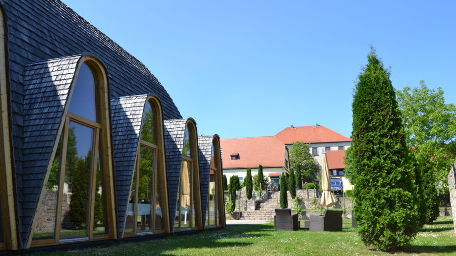 Weltdorfgemeinschaftshaus Maloca im Garten mit Sitzecken und Blick zum Schloss Auerstedt