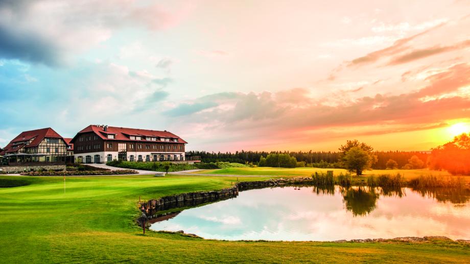Spa und Golf Resort mit Grünfläche und Teich im Vordergrund