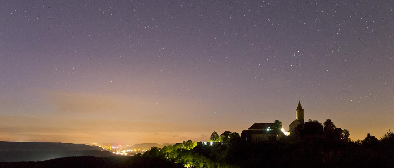 Blick auf die Leuchtenburg unter Sternenhimmel mit Lichtstadt Jena im Hintergrund